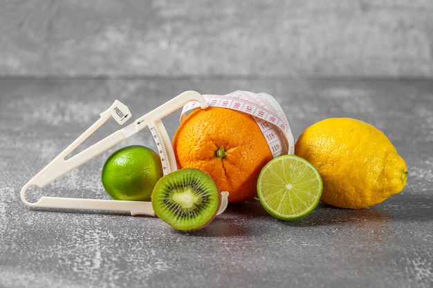 측정 테이프로 감싼 오렌지와 신선한 과일로 둘러싸인 캘리퍼스. 슬리밍의 개념은 셀룰 라이트를 제거하고 그림을 모양으로 만듭니다.