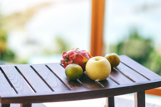 小さな木製のテーブルにオレンジ、洋ナシ、ドラゴンフルーツ