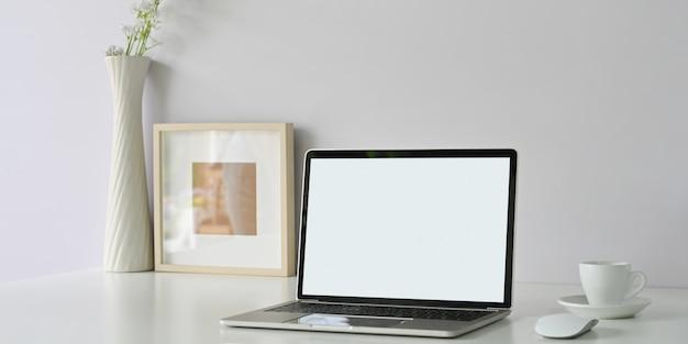 정돈 된 작업 공간은 흰색 빈 화면 컴퓨터 노트북, 액자, 커피 컵 및 꽃 화병으로 둘러싸여 있습니다.