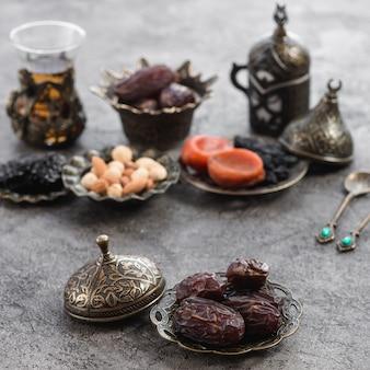 Органические финики на бронзовой тарелке перед сухофруктами; чай и орехи на бетонной поверхности