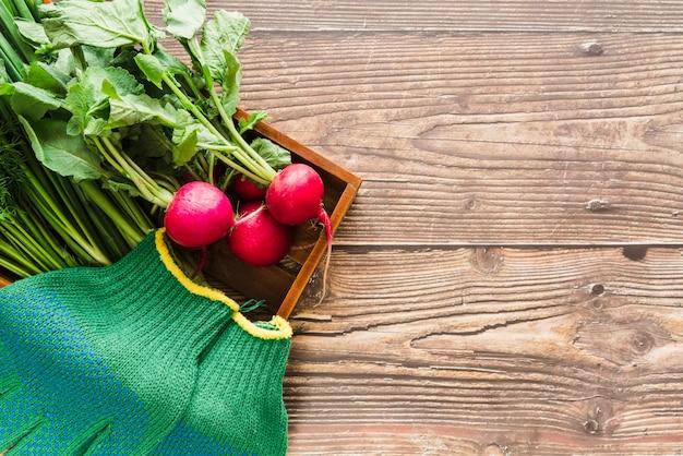 나무 책상 위에 나무 쟁반에 유기농 순무와 녹색 원예 장갑