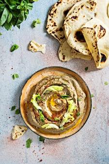 焼きナスのババガヌーシュのナスのピューレとスパイスハーブレタスと明るい背景のオリエンタルフラットブレッドのオリエンタル料理