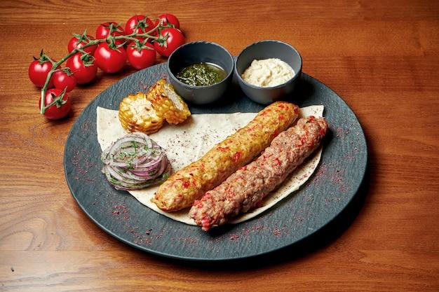 다진 고기에서 lavash와 녹색 소스를 곁들인 오리엔탈 요리 두 치킨과 양고기 케밥. 할랄 음식