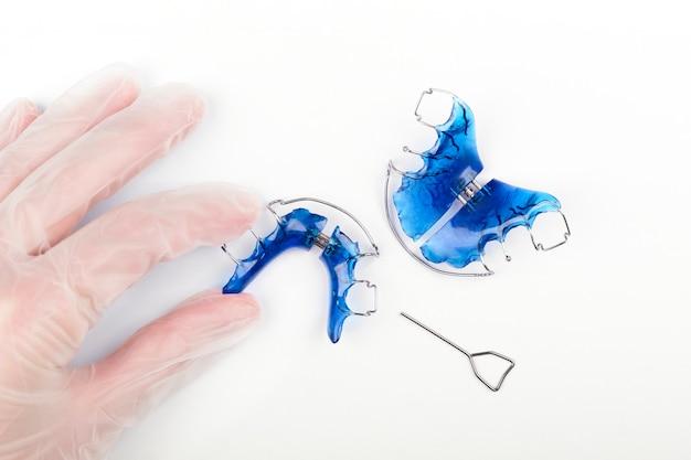 Ортодонт держит детский ортодонтический аппарат