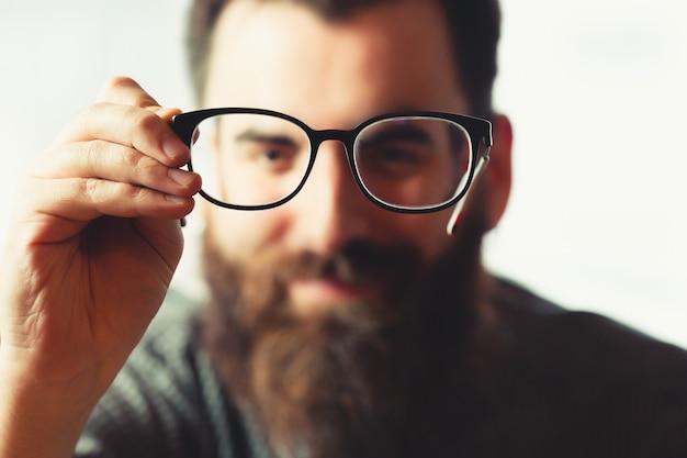 웃는 동안 카메라에 초점에 푸른 빛 안경 한 켤레를 들고 초점 힙 스터 남성 중