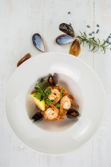 ティールのテクスチャーに魚介のリゾットを上から見た写真。フォークとスプーン、白ワイン1杯、テキストの場所