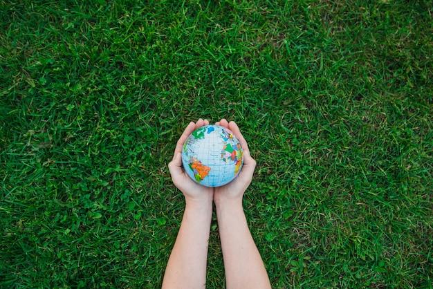 緑の草の上に地球儀を持っている手のオーバーヘッドのビュー
