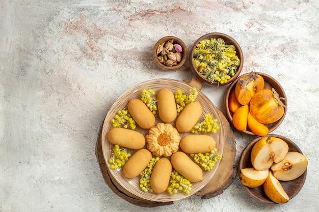쿠키와 마른 꽃과 과일 그릇의 오버 헤드 샷이 대리석 바닥에 퍼져 있습니다.