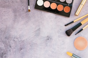 An overhead view beauty products for professional make-up on concrete background
