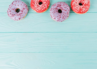 An overhead view fresh donuts arranged in a row on wooden table