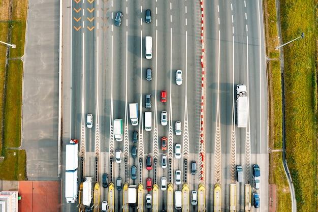 Вид сверху на загруженную платную дорогу с множеством автомобилей, стоящих в очереди, чтобы заплатить за проезд по шоссе.