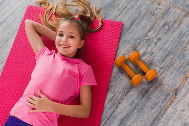 Вид сверху на девушку, лежащую на тренировочном мате возле гантели