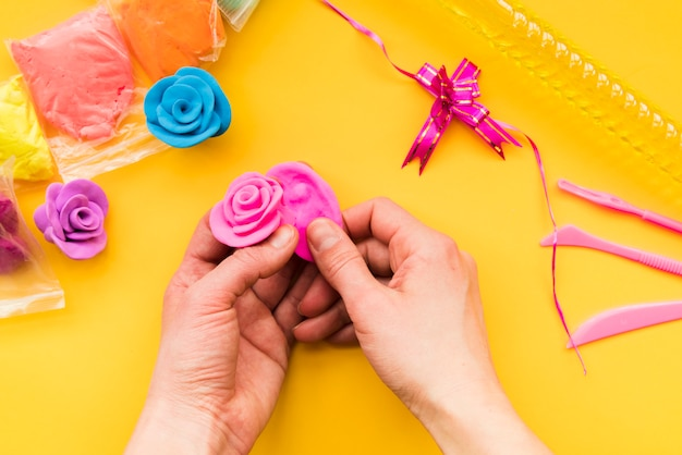 黄色の背景にカラフルなピンクのバラを作る人の手の俯瞰