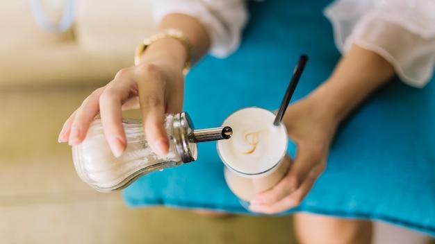 Вид сверху женщины, добавляющей сахар в стакан латте макиато