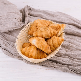 An overhead view of baked croissants in the wicker basket