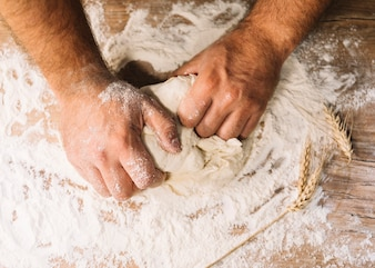 An overhead view of baker's hand kneading with wheat flour on table