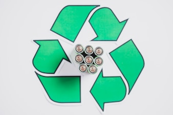 An overhead view of batteries in recycle icon on white backdrop
