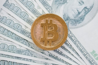 An overhead view of bitcoins over the us dollar currency bank notes