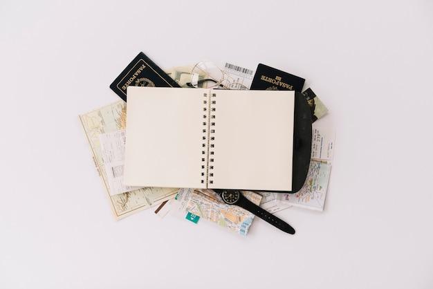 パスポートと白い背景にマップで空白のスパイラルノートブックのオーバーヘッドビュー