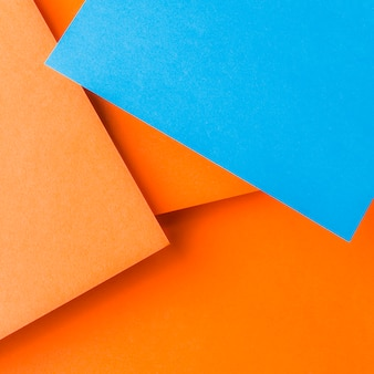 An overhead view of blue craft paper over the plain orange background