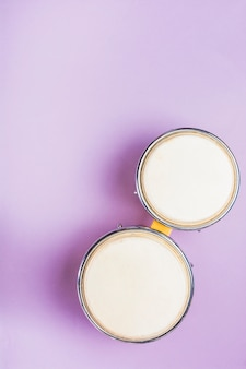 An overhead view of bongo drum on purple background