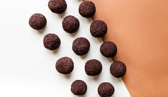 An overhead view of brigadeiro arranged in row on dual background