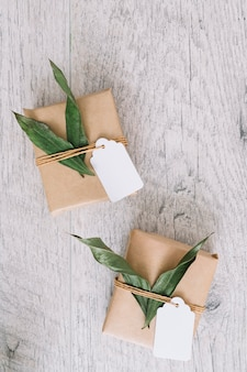 An overhead view of brown wrapped gift boxes with tag on wooden table