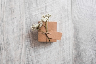 An overhead view of cardboard box tied with tag and baby's-breath flowers on wooden desk