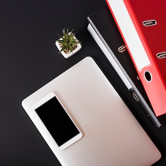 An overhead view of cell phone on laptop; succulent plant and paper files against black background