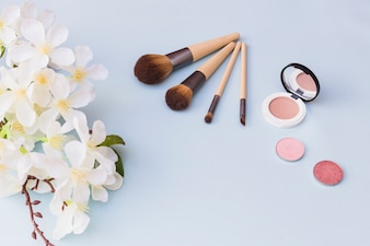 An overhead view of cherry blossom twig; makeup brush; blusher on blue background