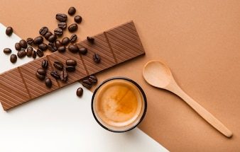 An overhead view of chocolate bar; roasted coffee beans with coffee glass and spoon