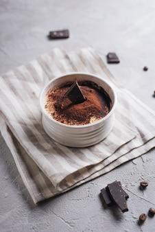 Вид сверху десерт шоколадный лось в керамической белой миске на салфетке