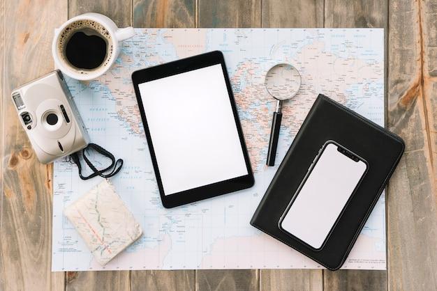 コーヒーカップのオーバーヘッドビュー。カメラ;デジタルタブレット;携帯電話;虫めがね、日記、地図、木製、テーブル