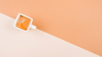An overhead view of coffee cup on dual background