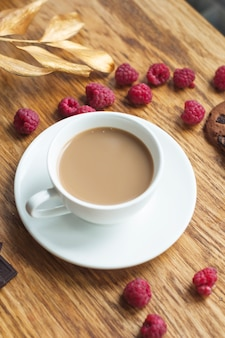 An overhead view of coffee cup on saucer with fresh raspberries on wooden table