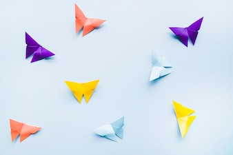 An overhead view of colorful origami paper butterflies on blue background