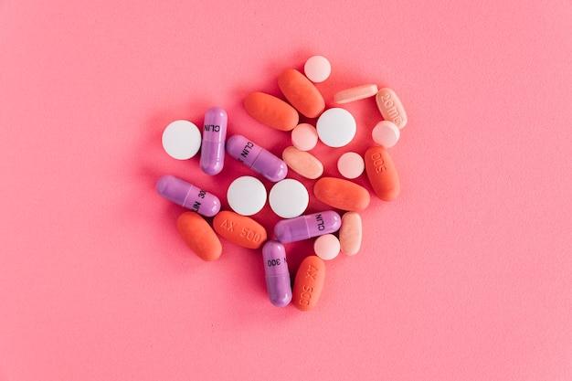 분홍색 배경에 화려한 알 약의 오버 헤드보기