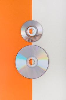 주황색과 흰색 이중 배경에서 컴팩트 디스크의 오버 헤드보기