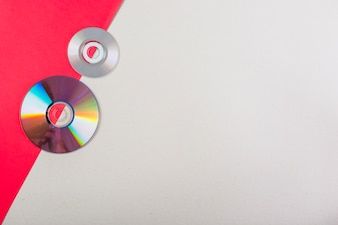 An overhead view of compact discs on red and white dual background
