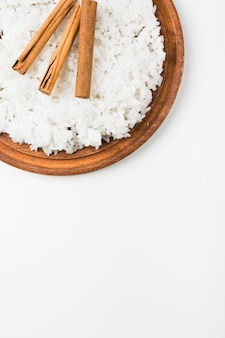 An overhead view of cooked rice with cinnamon sticks on wooden plate against white background