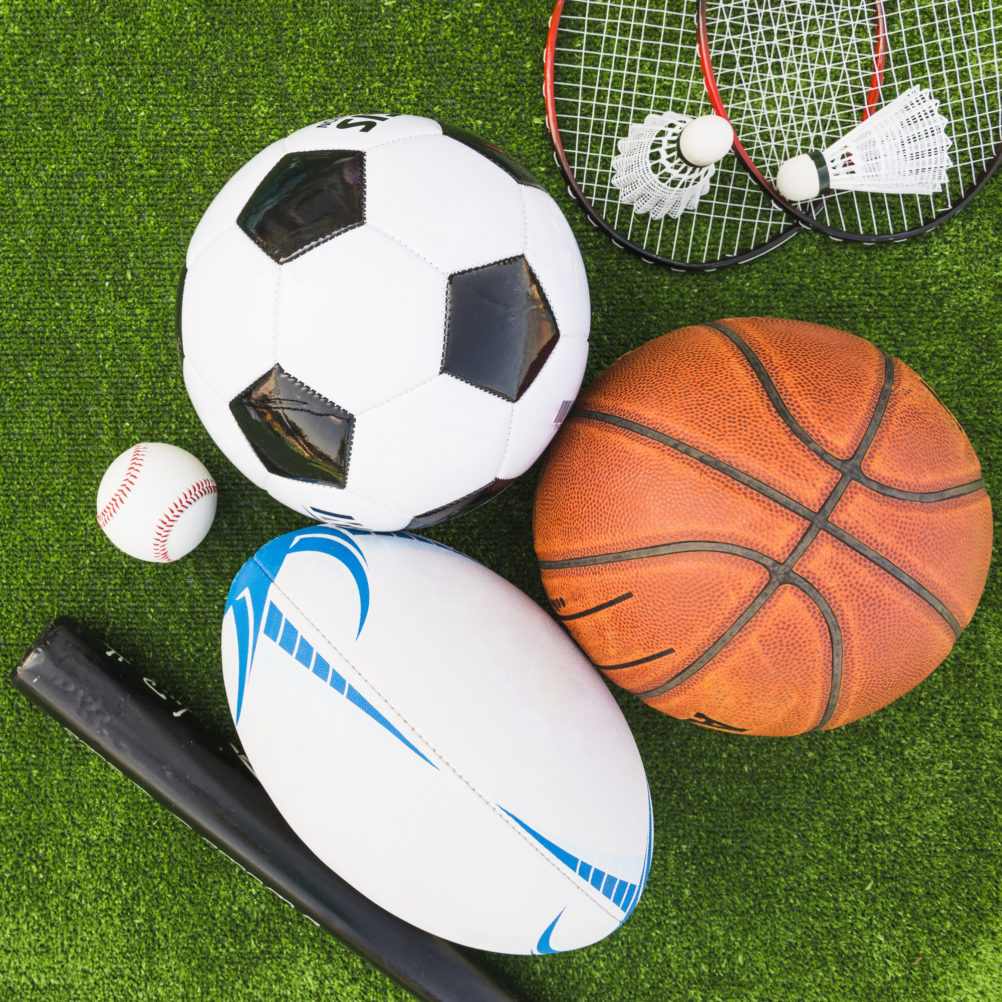 An overhead view of different type of sports equipment on green turf