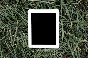 An overhead view of digital tablet with black screen on green grass