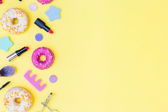 An overhead view of donuts; lipstick; eyelash curler; makeup brush and toe divider on yellow background
