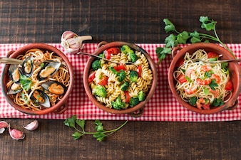 An overhead view of earthenware with different type of pasta on tablecloth