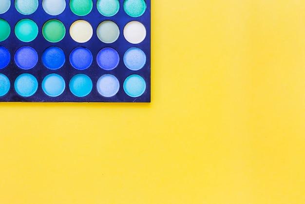 Верхний вид палитры тени для век на желтом фоне