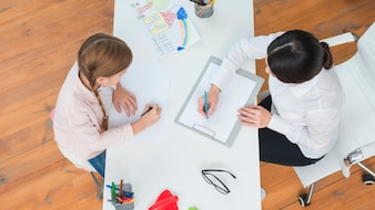An overhead view of female psychologist making note sitting with the girl drawing on paper