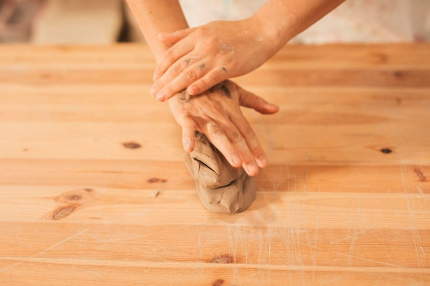 Вид сверху женских рук над замешенной глиной на деревянном столе