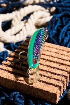 Вид сверху рыболовной приманки на пробковой доске над рыболовной сетью