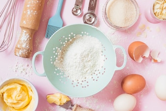 An overhead view of flour; eggs; butter and equipments on pink background