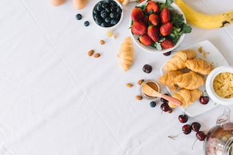 An overhead view of fresh fruits and croissant on dinning table